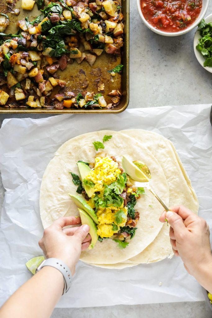 Sheet pan veggies and bacon, eggs, cilantro, avocado, and salsa come together in these loaded breakfast-style burritos. So flavorful and easy! Vegetarian option, too.