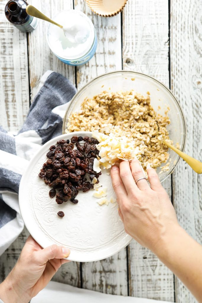 adding raisins and coconut to make oatmeal cups