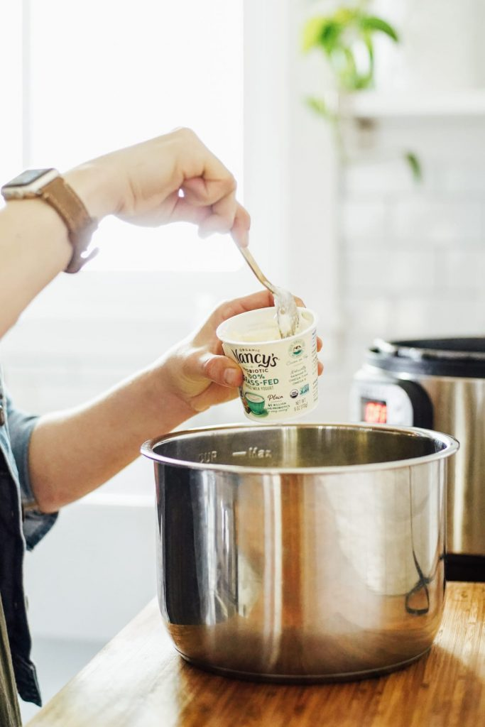Scooping the yogurt starter into the milk to make homemade yogurt