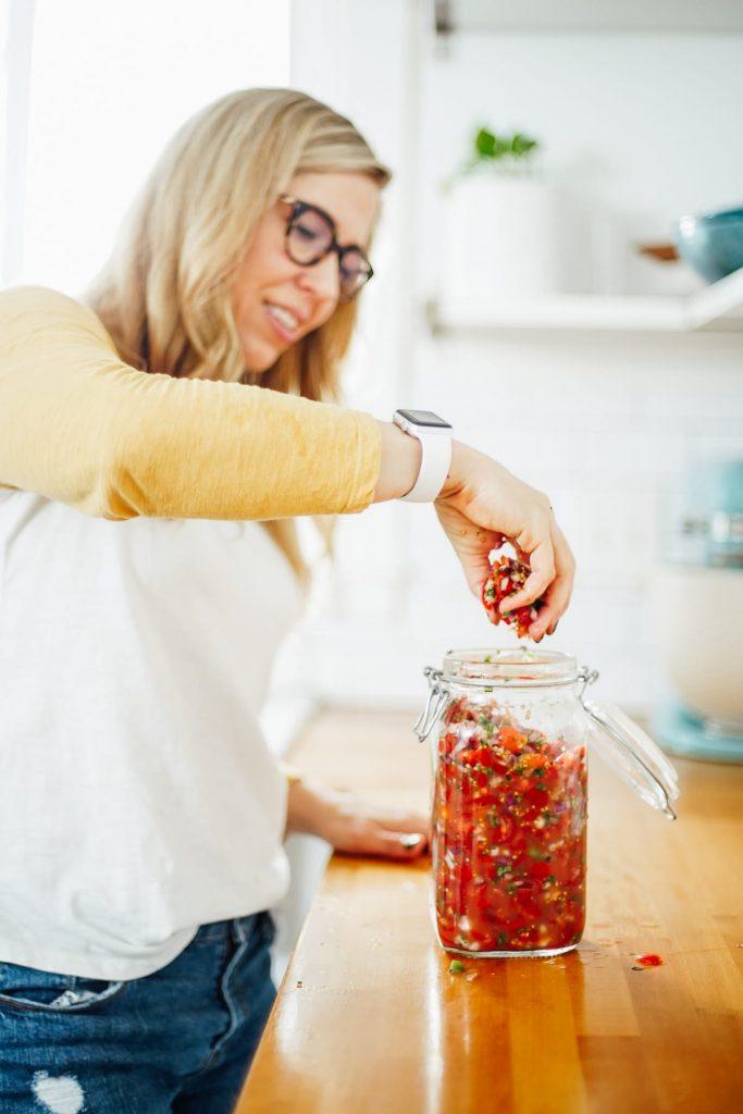 adding salsa to a jar to ferment