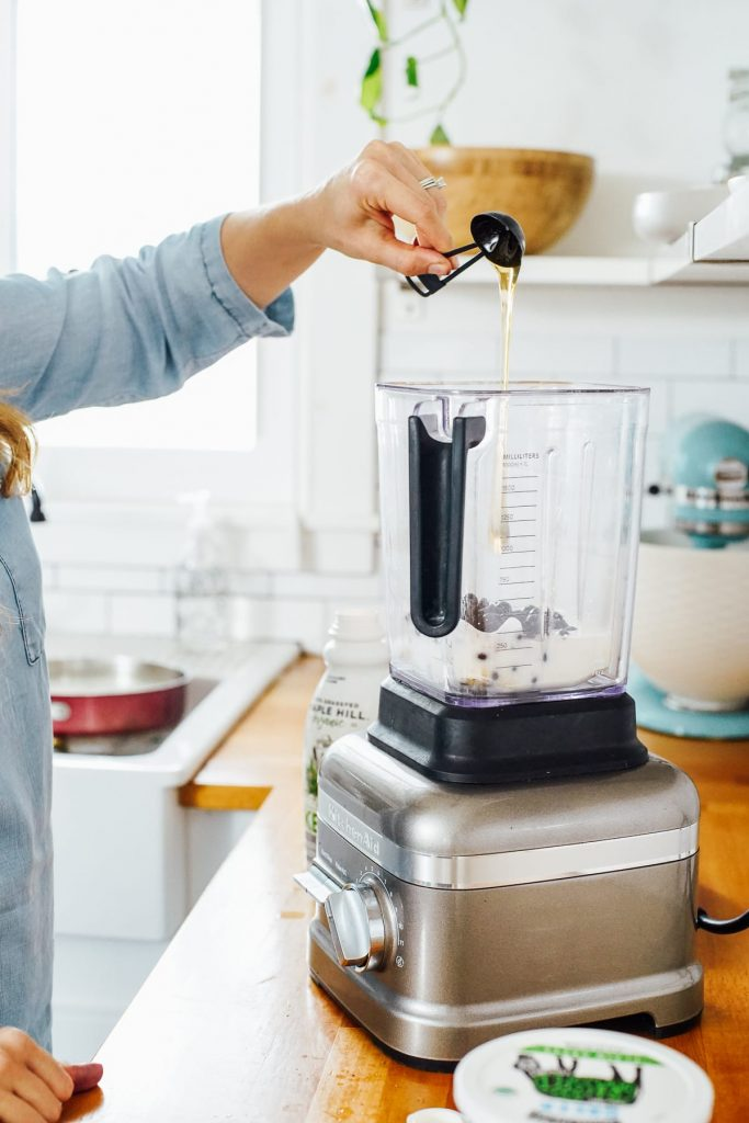 adding honey to the blender