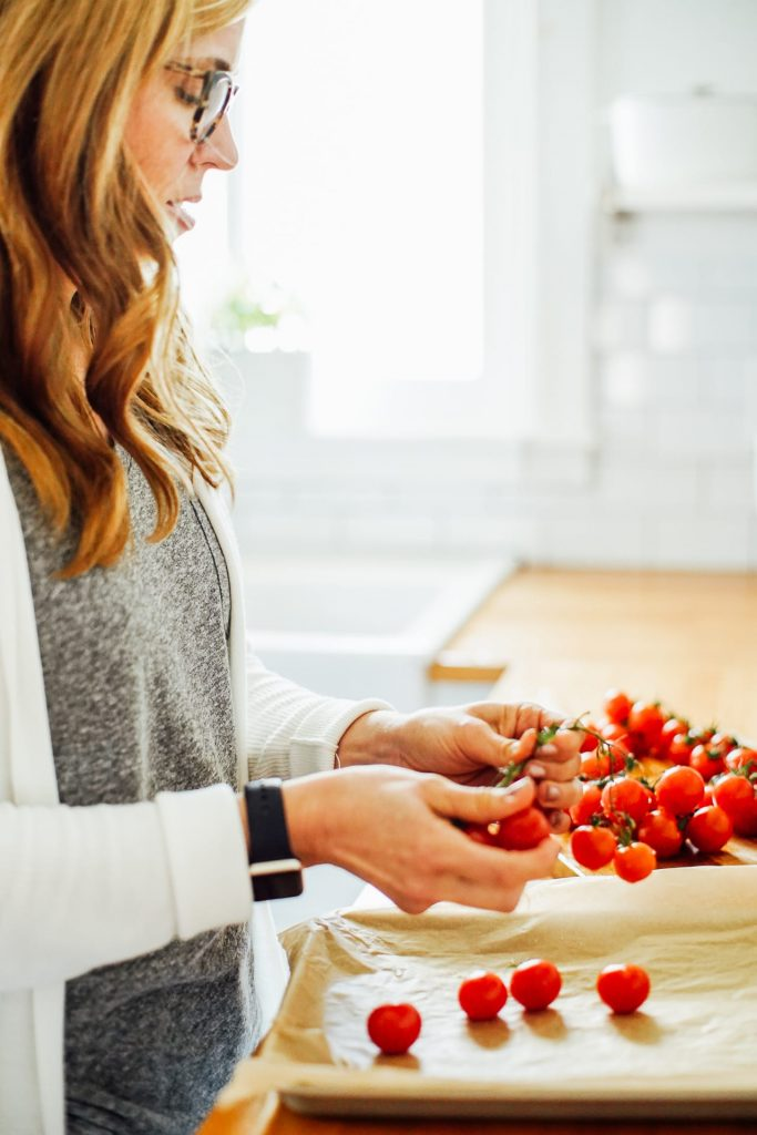 preparing tomatoes on a sheet pan to be roasted