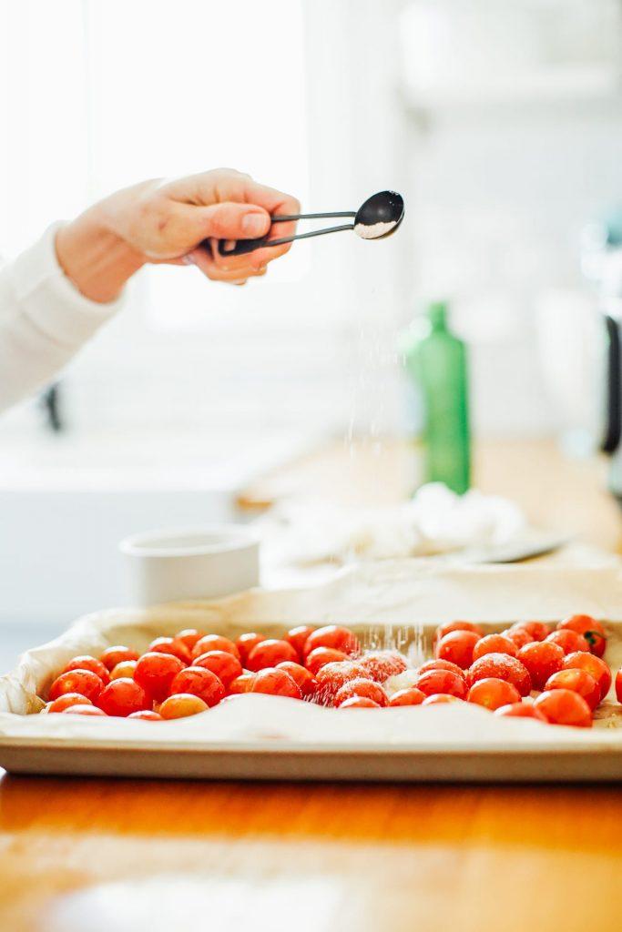 sprinkling salt over tomatoes to roast