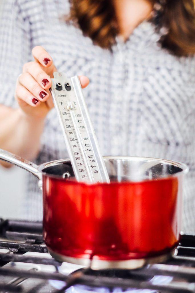 Adding thermometer to saucepan to make marshmallows