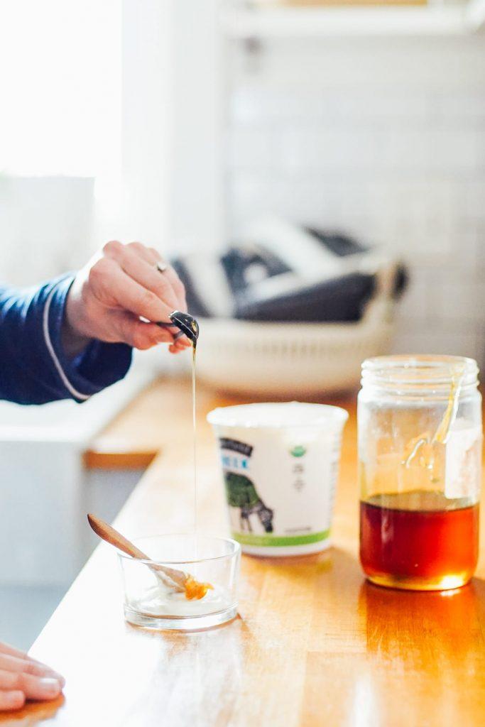 Adding honey to yogurt to make face mask