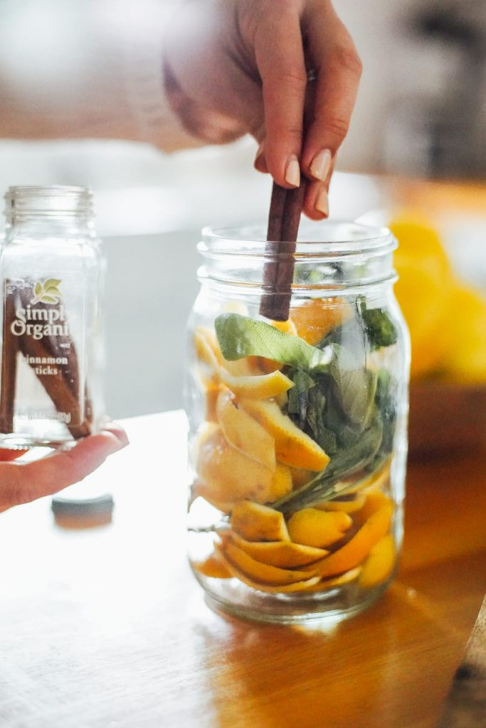 adding cinnamon stick to the jar with orange peels and herbs
