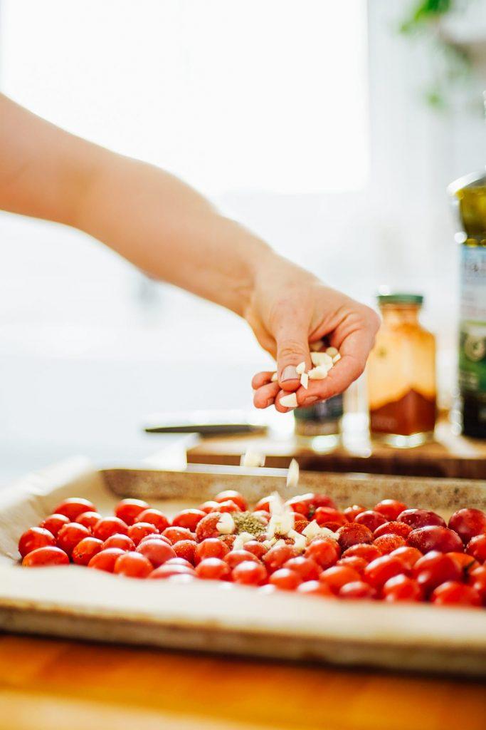 adding garlic to tomatoes