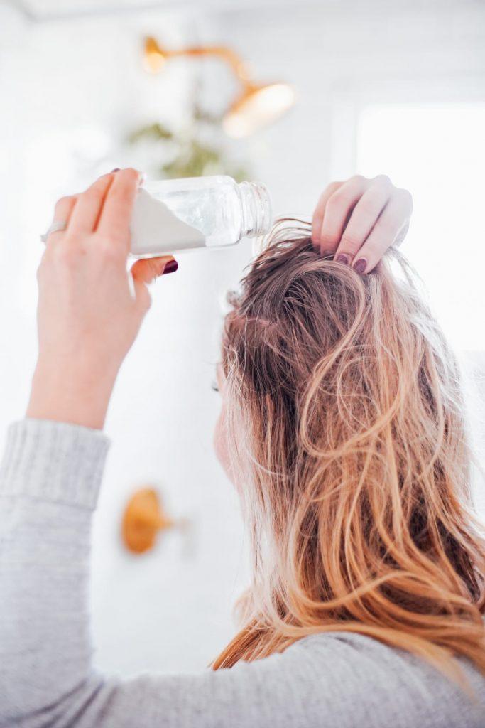 applying dry shampoo to hair