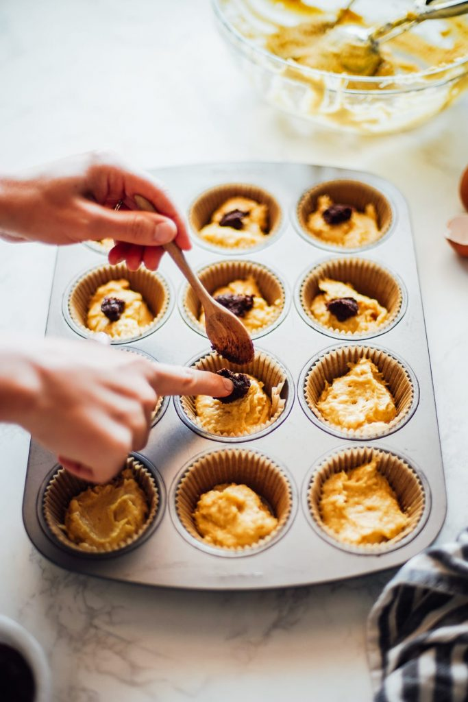 einkorn muffin batter with cinnamon swirl mixture spooned on top